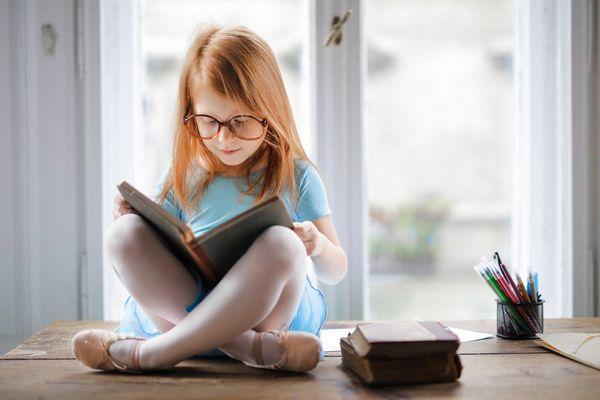 Asztal tetején egy szemüveges kislány törökülésben ül és könyvet olvas.