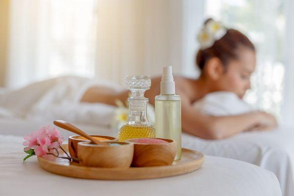 Háttérben egy fiatal lány hason fekve várja a masszőrt, előtte egy tálcán virág, illóolajok és fürdősók tálakban.
