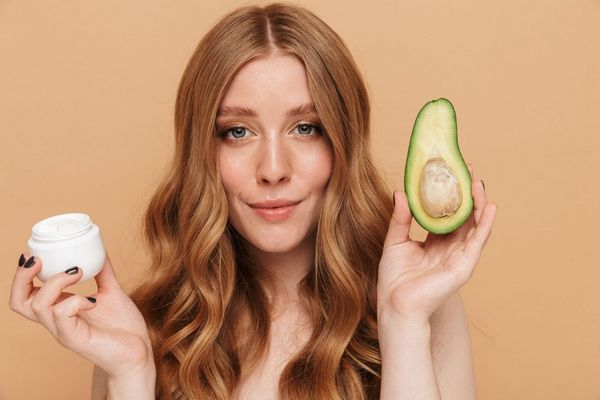 Egy vörös hajú lány jobb kezében egy arckrémet, a bal kezében egy félbe vágott avokádót tart.