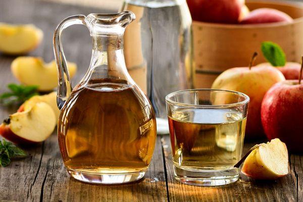 Egy asztalon egész és félbevágott almák, mellettük üvegkancsóban és üvegpohárban almaecet.