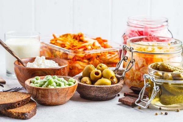 Probiotikus ételek kis tálakban és üvegekben, túró, savanyúság, savanyú uborka, savanyú káposzta, vegyes savanyúság, olívabogyók és teljes kiőrlésű kenyér.