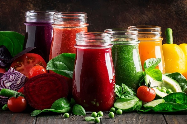 Egy asztalon zöldségek, mellettük üvegpoharakban a belőlük készült levek, cékla, paradicsom, uborka, borsó, vörös káposzta, spenót, paprika.