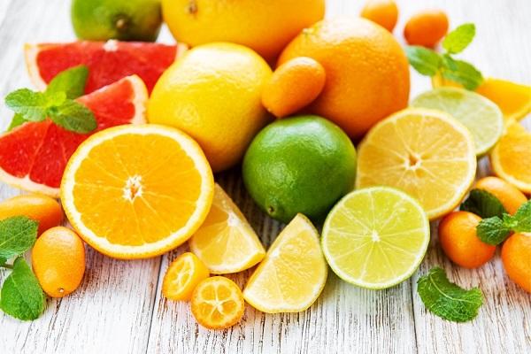 Egy asztalon egész és félbe vágott citrusos gyümölcsök, narancsok, citromok grapefruit, lime.