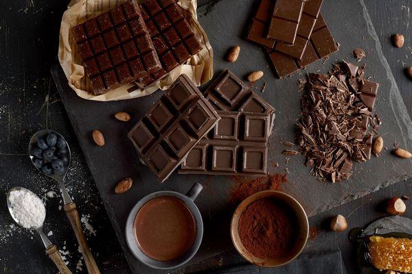 Egy asztalon étcsokoládék táblában és reszelve, kakaópor egy bögrében, mellette kakaóbabok, mogyoró, méz és fekete áfonya.