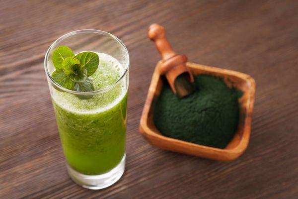 Egy asztalon kis tálban őrölt spirulina alga, mellette üvegpohárban spirulina algaporból készült ital.