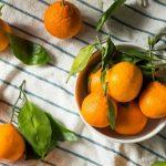 Egy csíkos terítőn egy tálban és mellette narancsok és leveleik.