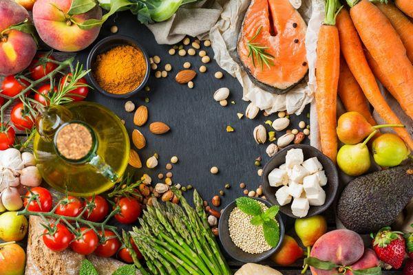 Egy asztalon sok egészséges zöldség és gyümölcs, illetve magvak, sárgarépa, avokádó, eper, körte, spárga, paradicsom, hal, őszibarack, mandula, pisztácia, bab, fetasajt, fokhagyma, olívaolaj.