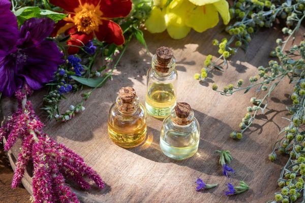Egy asztalon virágok, mellettük kis üvegekben illóolajok.