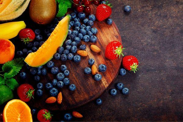 Egy asztalon gyümölcsök, fekete áfonyák, eprek, narancs, kivi, banán, lime, sárgabarack, cseresznye és mandulaszemek.