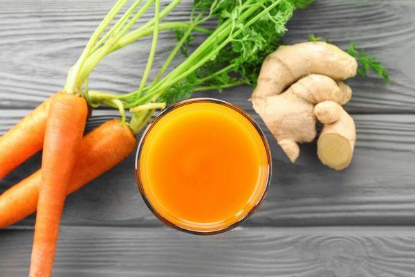 Egy asztalon sárgarépák, gyömbér, mellettük gyömbéres sárgarépalé egy pohárban.