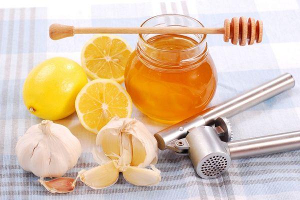 Egy asztalon üvegben méz, mellette egész és félbe vágott citromok, fokhagymák és fokhagymanyomó prés.