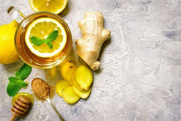 Egy asztalon egész és szeletelt gyömbér, citrom, méz, mentalevél, barna cukor és citromos tea.