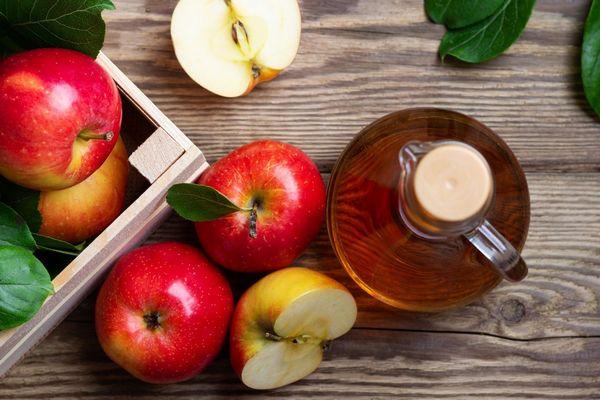 Egy asztalon piros almák, mellette egy üvegben almaecet.