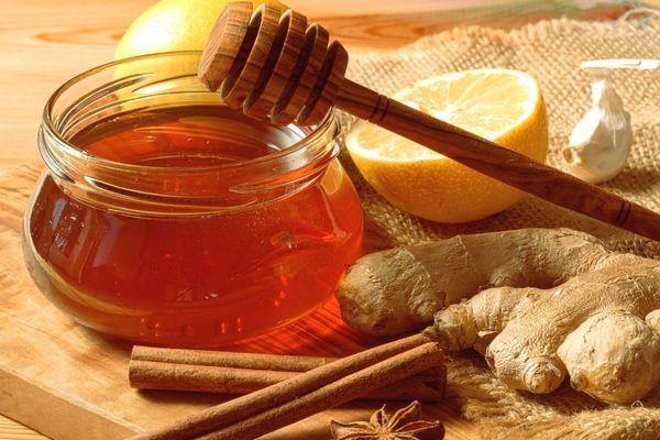 Egy asztalon üvegben méz, mellette gyömbér, csillagánizs, fokhagyma, fahéjrúd és félbevágott citrom.