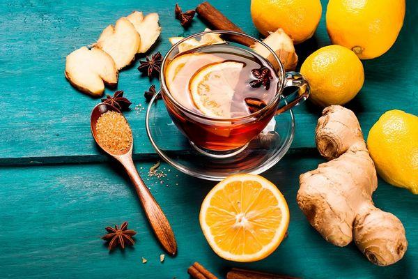 Egy asztalon üvegcsészében citromos tea, mellette egész és félbe vágott citromok, gyömbér, fahéjrudak, csillagánizs és kanálban barna cukor.