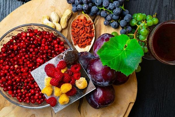 Egy asztalon tálakban resveratrolt tartalmazó gyümölcösk és magvak, goji magok, földimogyoró, szilvák, sárga és piros málna, vörös áfonya, fehér és fekete szőlő, egy üvegpohárba vörösbor. h