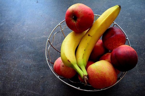 Egy fém kosárban piros almák és banánok.