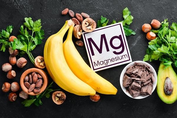 Egy sötét színű asztalon magnéziumot tartalmazó élelmiszerek, banánok, étcsokoládé, dió, mogyorók, kakaóbabok, avokádó és petrezselyemzöld.