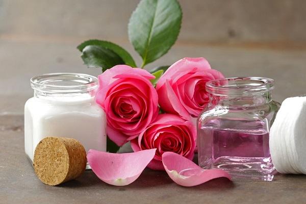 Egy szürke asztalon rózsaszínű rózsák, mellettük szirmok, üvegben rózsavíz és rózsavizes arckrém.