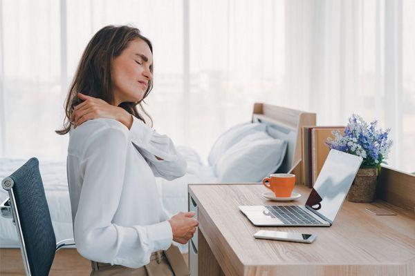 Egy irodában fiatal nő az íróasztalánál ül, bal kezével megfogja a fájós vállát.