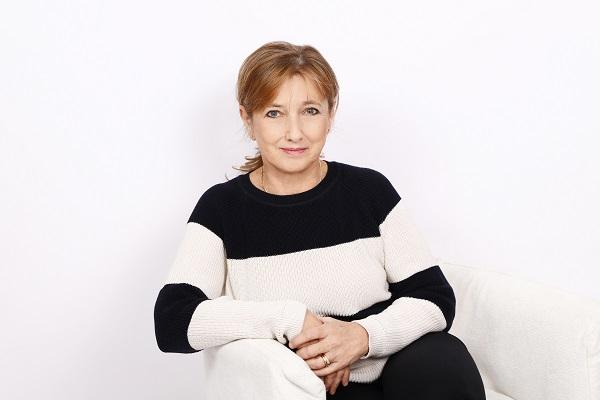 Szabó-Lopes Zsuzsa, fitoterapeuta egy fehér fotelben, fekete-fehér csíkos pulóverben ül.