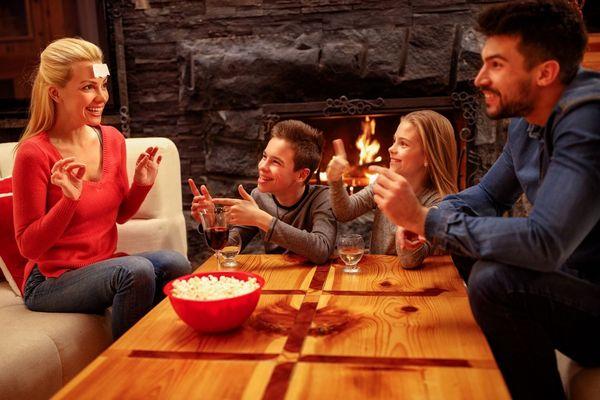 Egy család, a szülők a fiukkal és a lányukkal télen otthon társasjátékot játszik, az asztalon egy tálban popcorn.