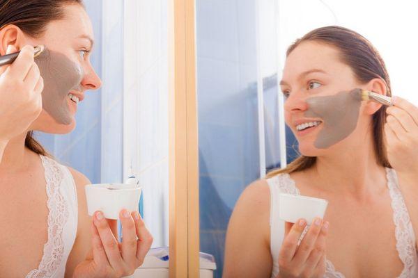Fürdőszobában fiatal hölgy a tükör előtt állva nézi magát amint az arcát iszappakolással bekeni.