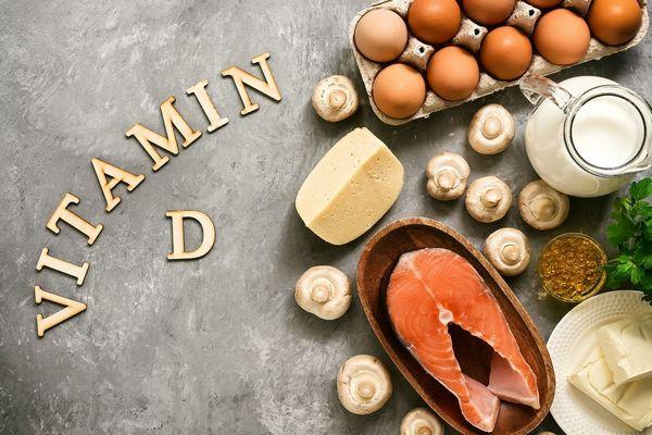 Egy asztalon D-vitamin felirat, mellette D-vitamint tartalmazó ételek, sajt, tej, vaj, gomba, tojás, lazac.