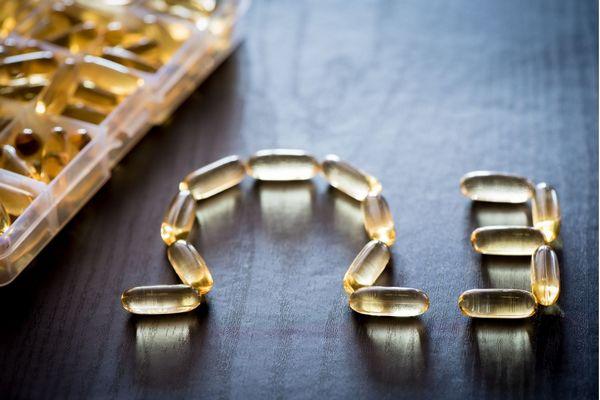Egy szürke asztalon halolajkapszulák egy tálban, mellette a kapszulából kirakott omega betű és egy 3-as szám.