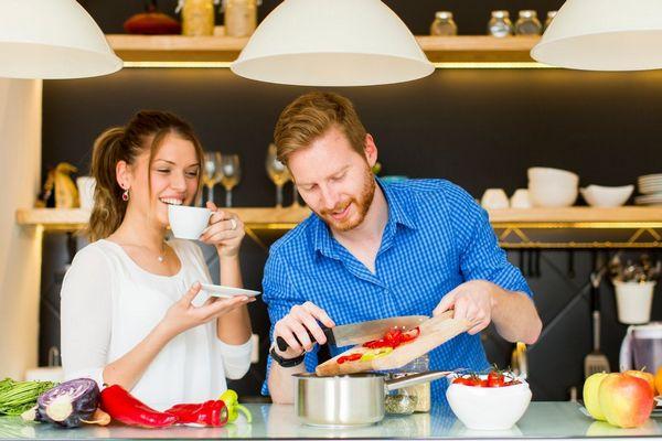 Egy fiatal házaspár a konyhában főz, a hölgy mosolyog és teát iszik, a férj zöldséget vág fel.