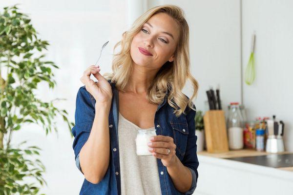 Fiatal hölgy a konyhájában natúr joghurtot eszik, közben mosolyog.