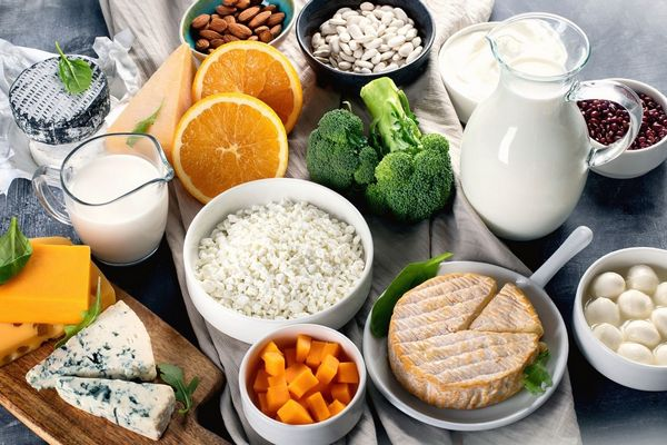 Egy asztalon sok kálciumot tartalmazó étel, tej üvegben, sajtot, brokkoli, narancs, mandula, bab, spenót.