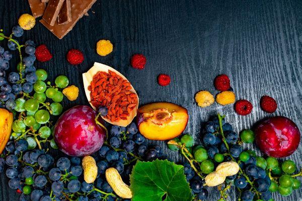 Egy asztalon sokféle polifenolt tartalmazó gyümölcs, szőlő, szilva, málna, sárga málna, őszi barack, goji bogyó, étcsokoládé, földi mogyoró.