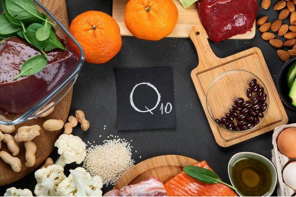 Egy asztalon koenzim-Q10-et tartalmazó ételek, máj, spenót, narancs, mandula, vörös hús, bab, avokádó, mogyoró, karfiol, tojás, olaj, szezámmagok, lazac.