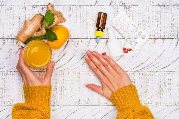 Egy asztalon sárga pulóvert viselő nő bal kezében gyömbéres narancslevet tartalmazó üvegpoharat tart, jobb kezével elutasító mozdulatot tesz gyógyszerek felé.
