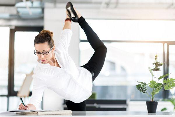 Egy fehér blúzos fiatal nő az irodában munka közben tormázik, jobb kezével ír, bal kezével a felemelt lábát tartja.