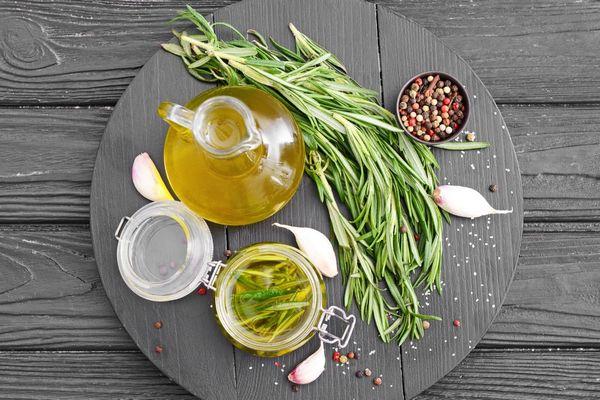 Egy szürke asztalon üvegcsében rozmaringolaj, rozmaringos olívaolaj, mellettük rozmaringágak, fokhagymagerezdek, színes bors szétszórva.