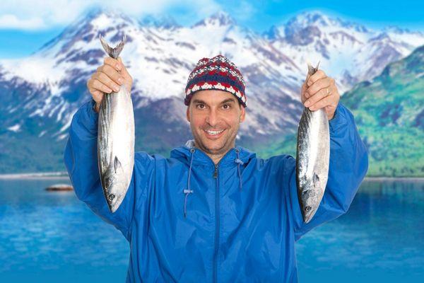 Egy férfi télen egy tó partján két halat emel fel a kezével.