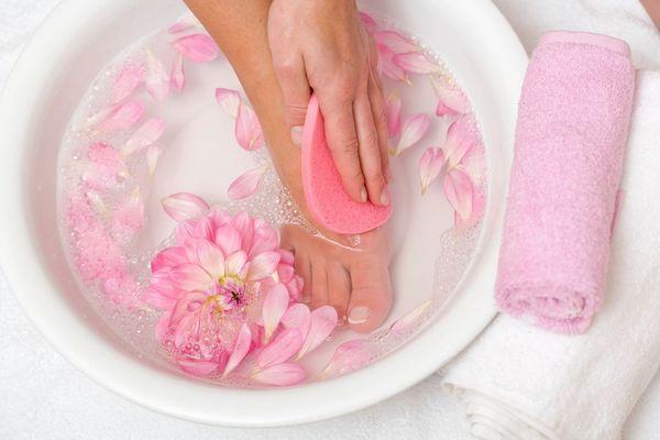 Fehér lavórban egy hölgy a lábát áztatja, a vízben rózsaszínű virágok, mellette fehér és lila törölköző.