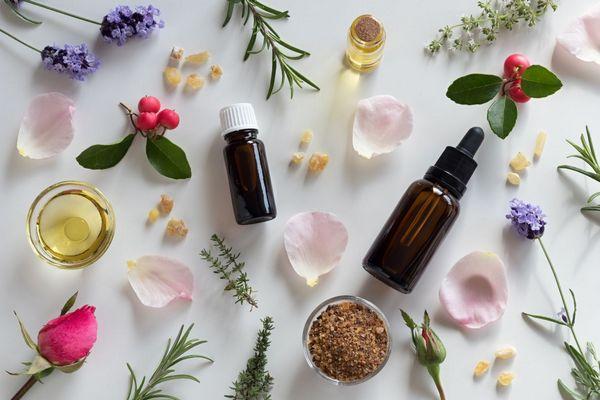 Egy asztalon gyógynövények és üvegcsékben illóolajok, rózsa, levendula, rozmaring virágszirmok.