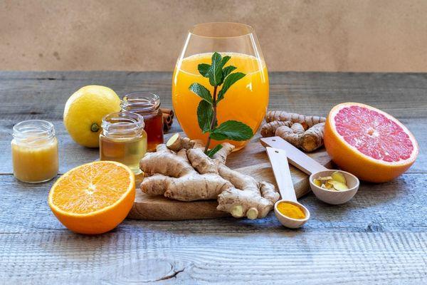 Egy asztalon immunitásfokozó elixírital egy üvegpohárban, mellette narancs, grapefruit, gyömbér, méz és kurkuma.