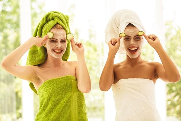 Két fiatal hölgy zöld és fehér törölközőben arcmaszkban nevet, miközben uborkaszeleteket mutatnak fel.