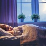 Lilás színű hálószobában kislány alszik az ágyában, az ablakban virágok.