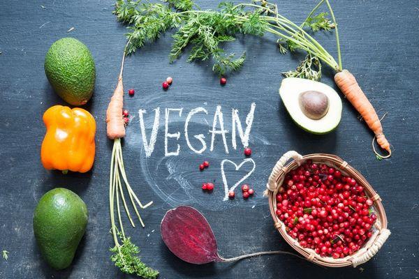 Egy szürke asztalon vegan felirat, körülötte zöldségek és gyümölcsök, sárgarépa, cékla, avokádó, sárga paprika, egy tálban vörös áfonya,