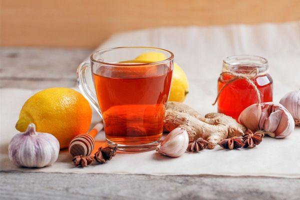 Egy asztalon üvegben méz, mellette üvegcsészében tea, citrom, fokhagyma, gyömbér, és csillagánizsok.