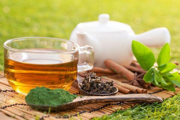 Egy asztalon egy üveg csészében immunitásfokozó zöld tea, mellette fehér teáskanna és egy fakanálban őrölt zöld tea.