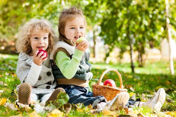 Egy kertben két óvodás gyerek a fűben ülve almát eszik.