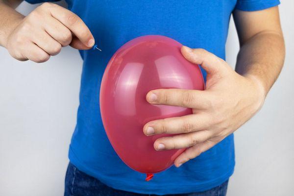 Egy kék pólós fiatal férfi hasa előtt rózsaszínű lufit tart, jobb kezével egy gombostűt a lufi felé emeli.