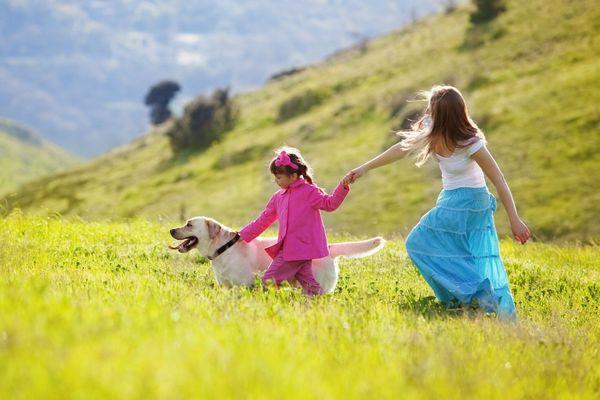 Hegyes-völgyes környezetben egy anya a kislányával és a kutyájukkal boldogan szaladgál.