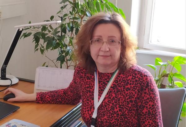 Dr Szekeres Mária, főiskolai docens piros pulóvereben ül az irodájában az íróasztalánál